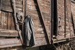 Vintage leather male jacket hanging on wooden railway wagon wall