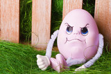 pink easter egg sit on grass with fance