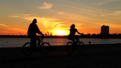 Silhouette Couple Riding Bikes At Sunset