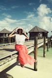 Girl on a wooden bridge near the water bungalows