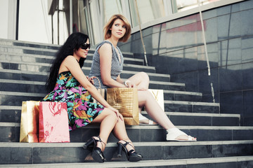 Two young women with shopping bags sitting on the mall steps