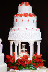 White wedding cake decorated with red flowers