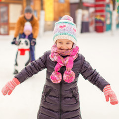 Adorable little girl on skating rink with father and little