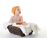 Kid in a pumpkin hat sitting in a basket