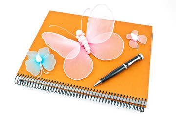 Stack of spiral notebooks with  butterflies and pen isolated on