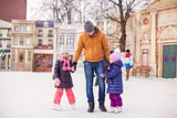 Little girls with young father enjoying skating