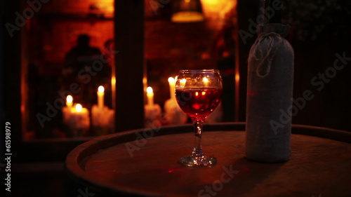 Wine bottle with glass on the wooden barrel cozy bar still life