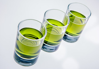 Three glasses of absinthe on white background
