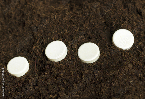White tablets in soil.