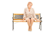 Mature lady sitting on wooden bench isolated on white background