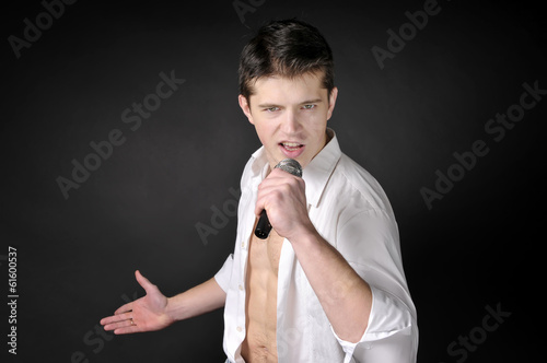 Expressively man singing with microphone on dark background.