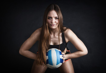 Young girl holding volleyball on black background