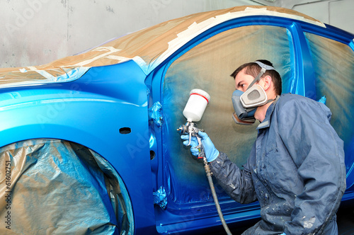 Worker painting blue car.