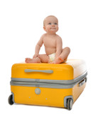 Happy child baby toddler sitting on yellow plastic travel suitca