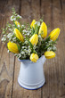 Bouquet of yellow tulips in vase on wooden background