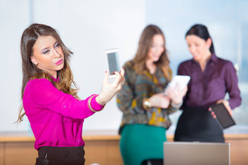 pretty business woman taking selfies with her smart phone