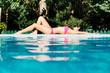 Sexy woman sunbathing at poolside