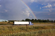 Semi truck driving under the rainbow