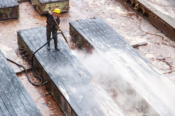 Worker cleaning dry dock in Gdansk shipyard