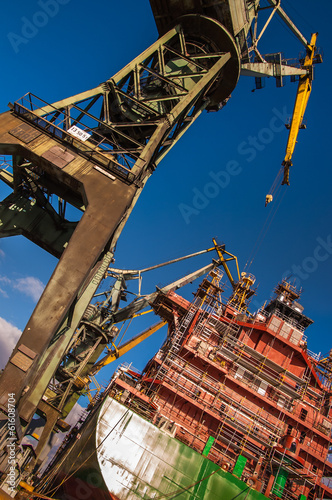 Tall cranes building an oil tanker at shipyard