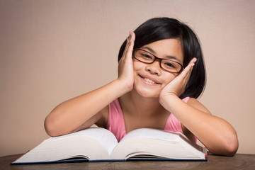 Girl wearing glasses reading at home