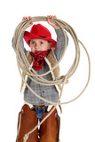 Playful boy in cowboy outfit holding rope wearing chaps