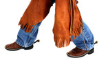 legs of a young cowboy wearing chaps spurs and boots poster