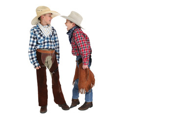 two young cowboys playing around taunting each other