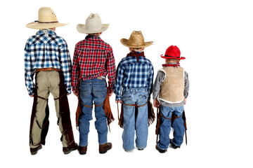 View of the backs of four young cowboys looking away