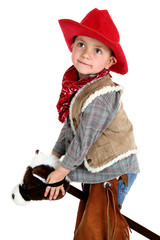 cute young cowboy riding toy stick horse