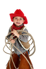 cute young cowboy playing with rope