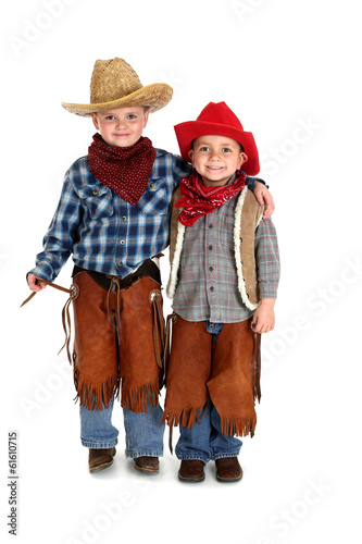 two brothers smiling hugging in cowboy outfits