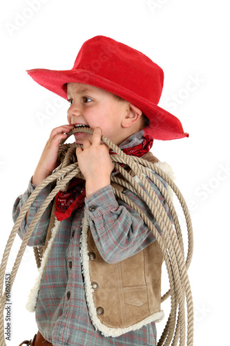 young cowboy playing with a rope wearing a red hat