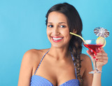 Woman holding tropical cocktail with decorative umbrella