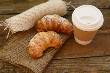 Rustic setting of a papercup and two croissants