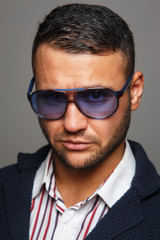 Portrait erious man wearing violet sunglasses