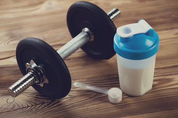 Bodybuilding components: protein shake with a dumbbell