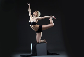 Image of seductive young dancer balancing on cube