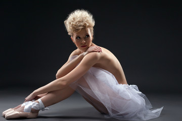 Shot of curly blonde ballerina posing in studio