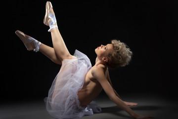 Elegant topless ballet dancer lying in studio