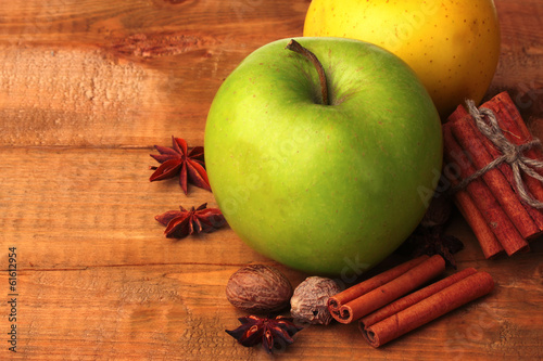 Cinnamon sticks, apples, nutmeg,and anise on wooden table