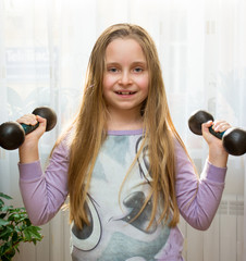 Portrait of happy little girl with dumbbells