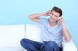 Guy sitting on sofa and  listening to music on blue background