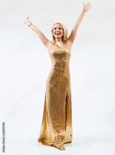 Beautiful female fashion model posing in gold dress
