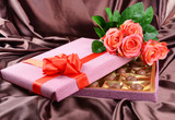 Delicious chocolates in box with flowers on brown background