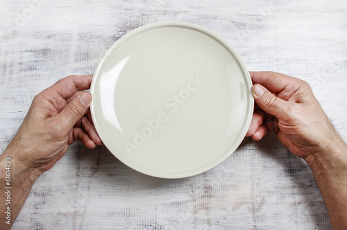 Hungry man waiting for his meal over empty plate on wooden table