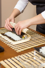 Hands of woman chef rolling up a japanese sushi