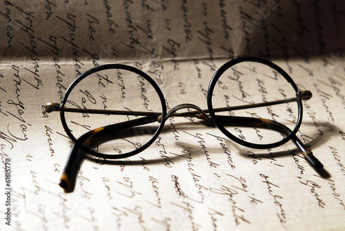 Old glasses on a letter - 61615770