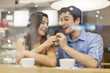 Cheerful couple talking on phone in cafe