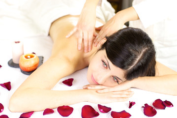 Dreaming during back massage in spa with flowers and candles